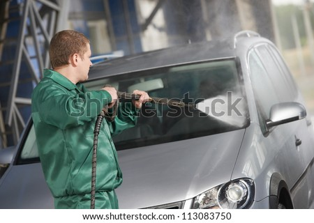 manual car washing cleaning with foam and pressured water at service station
