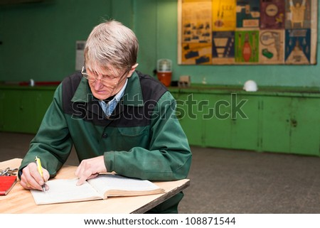 Manual Caucasian worker filling the journal in the workplace. Copyspace - stock photo