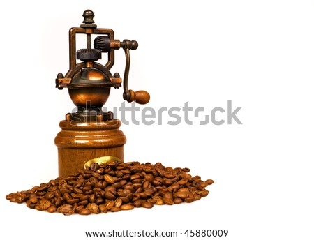 manual coffee grinder with coffee beans in the foreground - stock photo