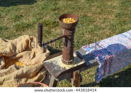 Manual Corncrusher corn grinding. Milling of different grains by hand in the old days. - stock photo