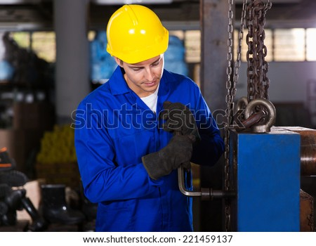 manual factory worker adjusting machine