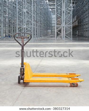 Manual Pallet Truck in Distributin Center Warehouse - stock photo