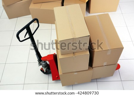 Manual pallet truck with carton boxes indoors - stock photo