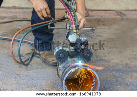 manual pipe cutting with oxy acetylene - stock photo