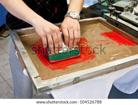manual screen printing - hand printing t-shirts - stock photo