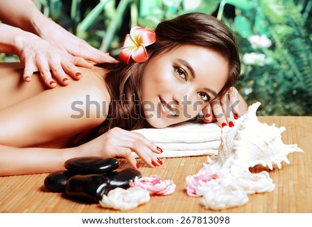 Manual therapy. Beautiful young woman getting massage at a spa salon. Healthcare, body care. - stock photo