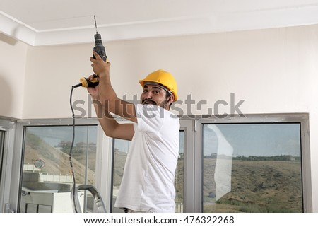 Manual Worker Drilling Hole at Ceiling