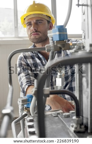 Manual worker looking away while examining machine in industry - stock photo