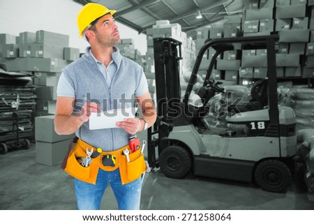 Manual worker looking away while writing on clipboard against warehouse worker loading up pallet - stock photo