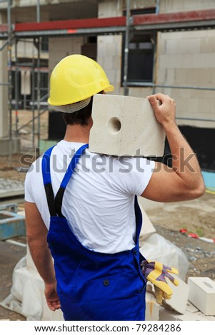 Manual worker on construction site carrying brick.