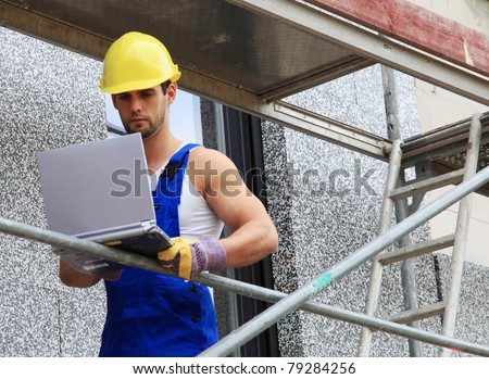 Manual worker on construction site using laptop.