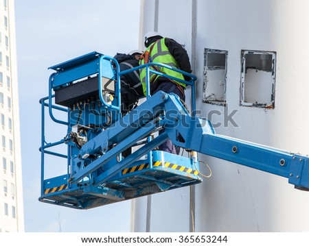 Manual worker on hydraulic lift - stock photo