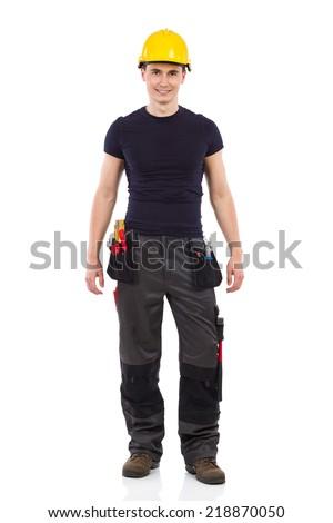 Manual worker posing in yellow helmet. Full length studio shot isolated on white. - stock photo
