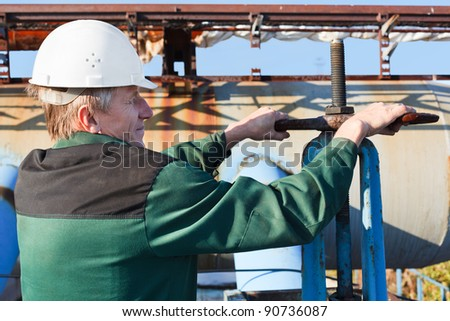 Manual worker turning big valve in industrial plant - stock photo
