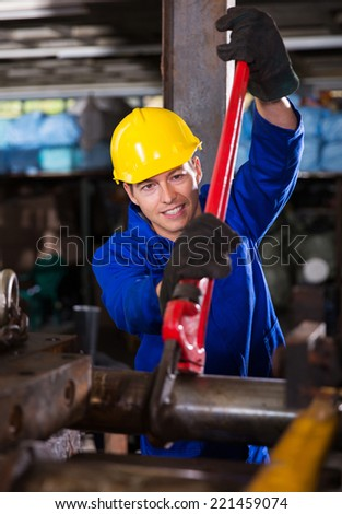 manual worker using wrench on industrial machine