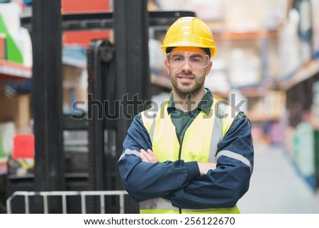 Manual worker wearing hardhat and eyewear in warehouse - stock photo