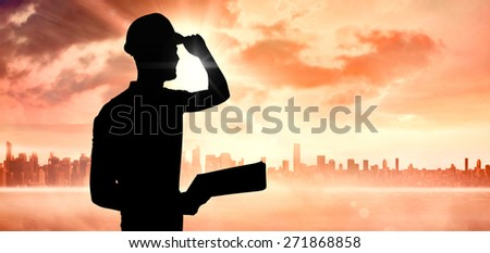 Manual worker wearing hardhat while holding clipboard against sun shining over city - stock photo