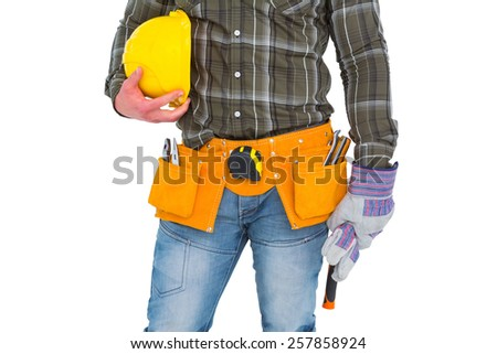 Manual worker wearing tool belt while holding gloves and helmet on white background - stock photo