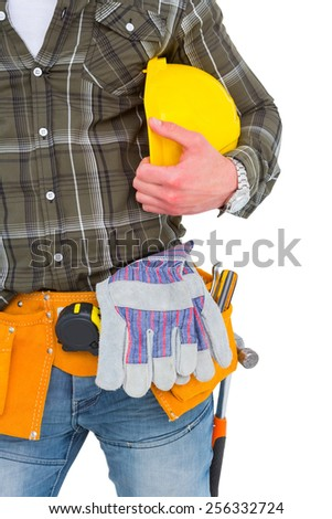Manual worker wearing tool belt while holding helmet on white background - stock photo