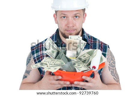 Manual worker with a hard-hat full of dollar bills and working instruments - stock photo