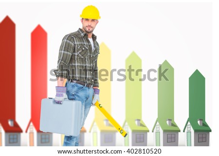 Manual worker with spirit level and toolbox against seven 3d houses representing energy efficiency