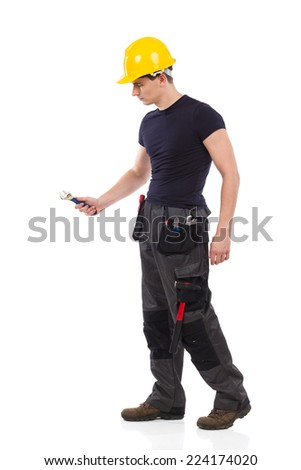 Manual worker working with a wrench. Full length studio shot isolated on white.