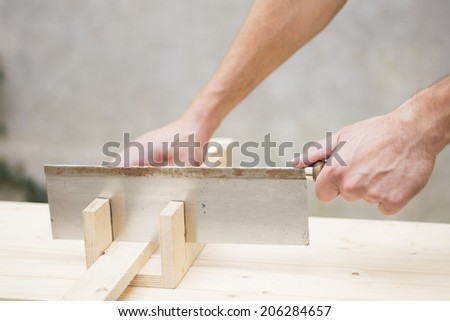 Manual worker working with wood saw and miter box
