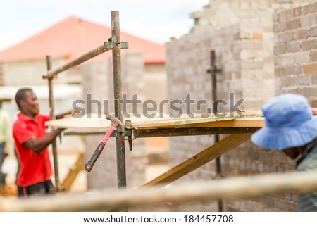 Manual workers building a house, working on construction site - stock photo