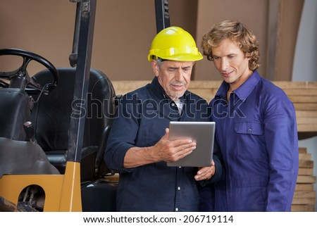 Manual workers using digital tablet together in workshop - stock photo