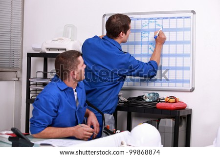 Manual workers writing on a calendar - stock photo