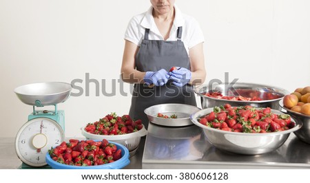 manufacture of jam with fruits with a a cut face woman who work for that - stock photo
