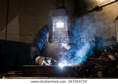 Manufacture worker welding metal at factory workshop with flying sparks - stock photo