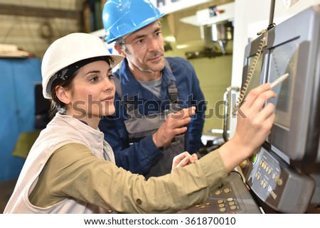 Manufacture workers working on electronic machine - stock photo