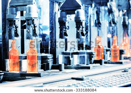 Manufacturing process of bottles in the glass factory - stock photo
