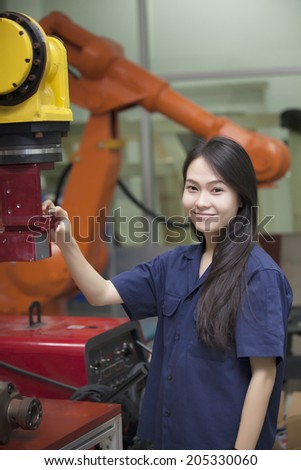 Manufacturing worker operating a robot machine - stock photo