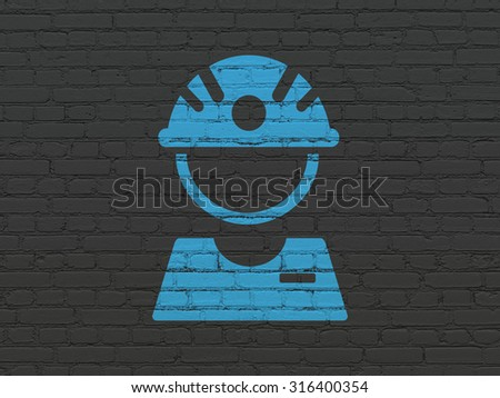 Manufacuring concept: Painted blue Factory Worker icon on Black Brick wall background - stock photo