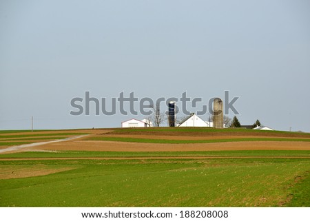 Many Acres on an Amish Farm in rural farmland as the land is prepared and fertilized for the upcoming Corn growing season - stock photo