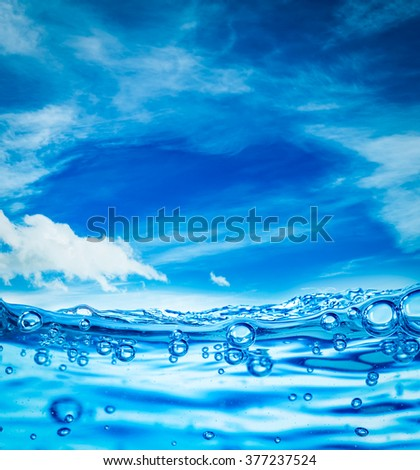 Many air bubbles in water close up, abstract water wave with bubbles on a background of blue sky - stock photo