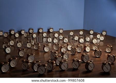Many alarm clocks on a wooden floor. Art installation. - stock photo