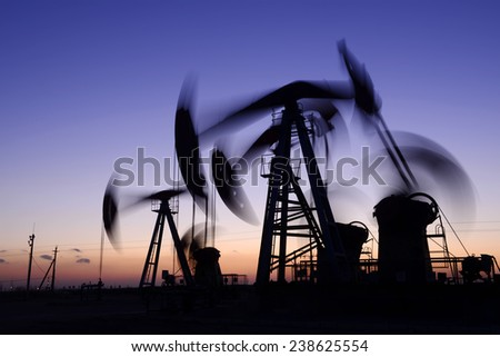 Many are operation of pumping unit, in the oil field in the evening   - stock photo