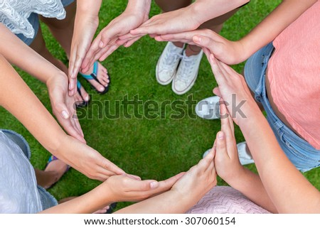 Many arms of young girls with hands making circle above green grass - stock photo