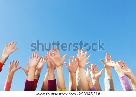 Many arms raised in the sky - stock photo