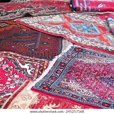 many Asian rugs for sale in the shop of fabrics and textiles