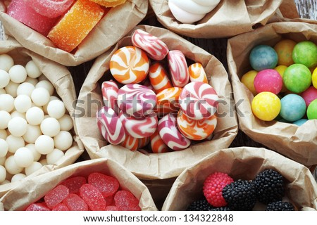Many assorted sweet sugar candies on vintage wooden background top view point - stock photo