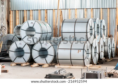 Many bended steel/metal sheet rolls in factory warehouse/workshop. Metalworking. Indoors. - stock photo