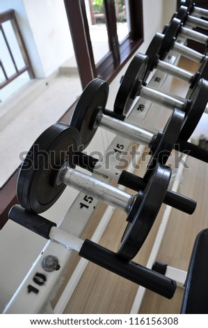 Many black dumbbell in the fitness room - stock photo
