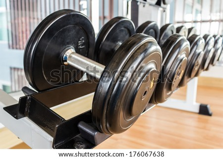 Many black dumbbell lined up in a fitness room. - stock photo