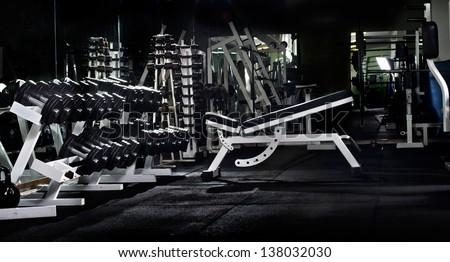 many black dumbbells in dark weight room, horizontal photo - stock photo