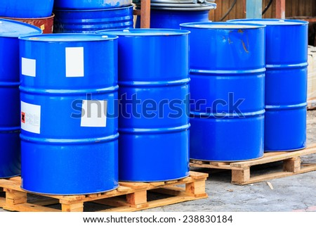 Many blue barrels standing on wooden pallets on a chemical plant - stock photo