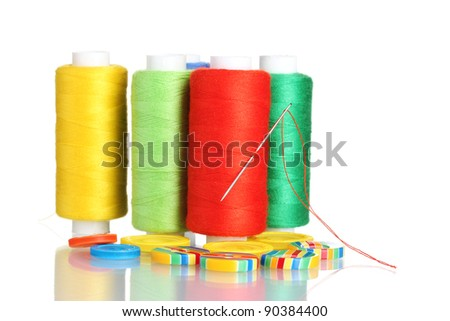 Many bobbin of thread with needle and buttons isolated on white